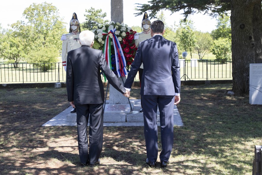 Slovenian President Borut Pahor and Italian President Sergio Mattarella, left, hold hands in Basovizza, near Trieste, Italy, Monday, July 13, 2020. The presidents of Italy and Slovenia met a several ceremonies on Monday linked to sorrowful incidents in their nations history and aimed at reinforcing reconciliation. In the area of Trieste, a port city near Italy's border with Slovenia, Italy's Sergio Mattarella and Slovenia's Borut Pahor held hands and observed a minute of silence at a monument to four anti-Fascist Slovenes, who were executed by Italian dictator Benito Mussolini's regime in 1930. The four became symbols the Slovene minority's resistance to Italian Fascism. (Francesco Ammendola, Italian Presidency via AP)