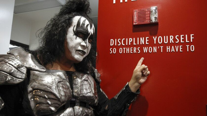 SAN DIEGO, February 7, 2019 | Kiss bass player Gene Simmons points to writing on a wall during a mee