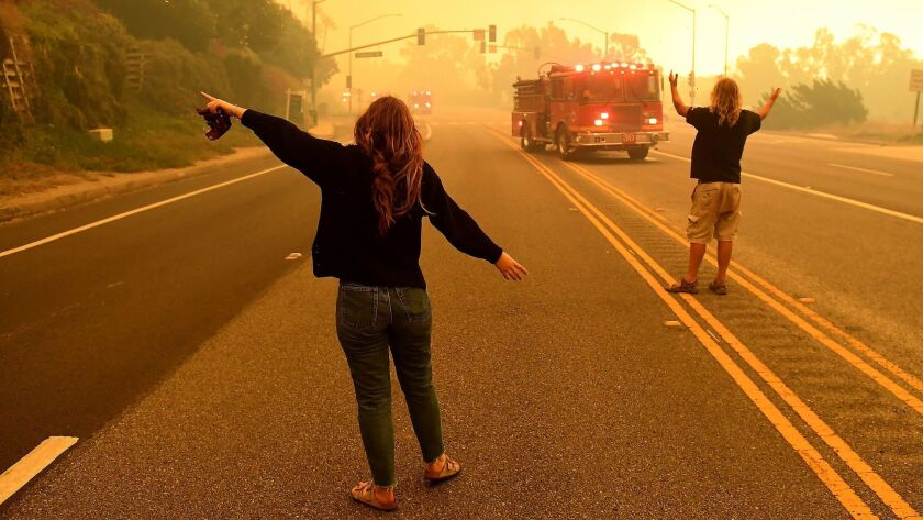 MALIBU, CALIFORNIA NOVEMBER 9, 2018-A father and daughter beg for a fire engine stop and protect the