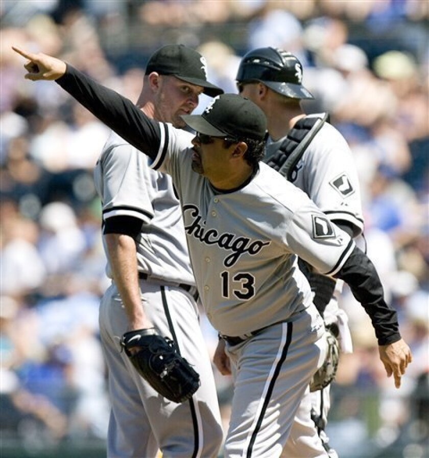Chicago White Sox manager Ozzie Guillen (13) signals to the bullpen as he takes out starting pitcher John Danks, back left, as A.J. Pierzynski looks on in the sixth inning of a baseball game against the Kansas City Royals, Sunday, May 31, 2009, in Kansas City, Mo. (AP Photo/Ed Zurga)