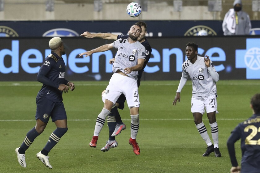 Rudy Camacho, center, of the Montreal Impact heads the ball in front of Kacper Przybylko of the Philadelphia Union in the second half. The Philadelphia Union becomes the first Philadelphia-area team to allow fans in the stands for their game against Montreal on Oct. 11, 2020, in Chester, Pa. (Charles Fox/The Philadelphia Inquirer via AP)
