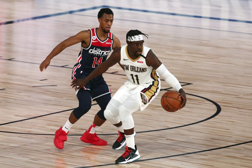 New Orleans Pelicans guard Jrue Holiday (11) handles the ball against Washington Wizards guard Ish Smith (14) during the fourth quarter of an NBA basketball game Friday, Aug. 7, 2020, in Lake Buena Vista, Fla. (Kim Klement/Pool Photo via AP)