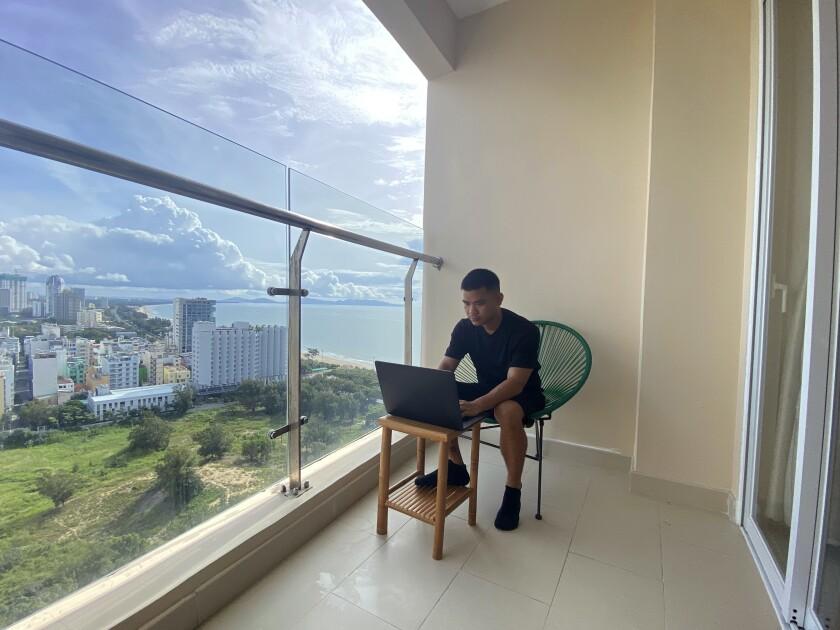 El periodista de AP Hau Dinh trabajando en el departamento de su pareja en Vung Tau (Vietnam), donde está confinado desde hace nueve semanas por un brote de COVID-19. Foto del 13 de septiembre del 2021. (AP Photo/Mathieu Le Besq)