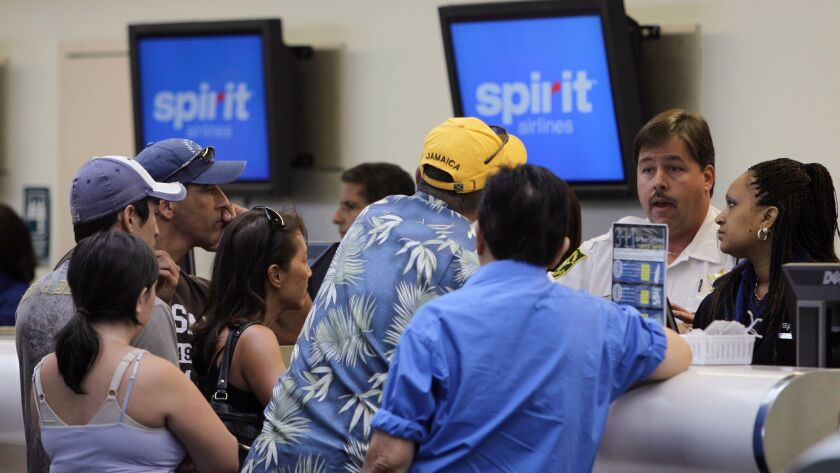 FILE - In this June 12, 2010, file photo, stranded passengers stand at the Spirit Airlines ticket co