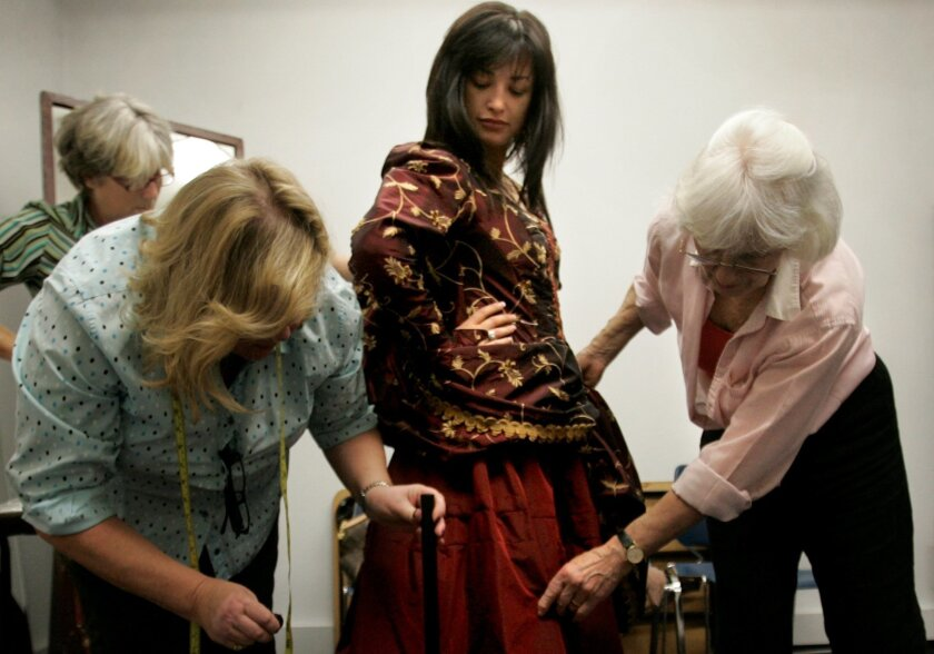 As costume shop manager Missy West (background) watches, dressers Tara Bach-Richards (left) and Crystal Yount fit one of the costumes on Nino Surguladze, who plays Carmen.