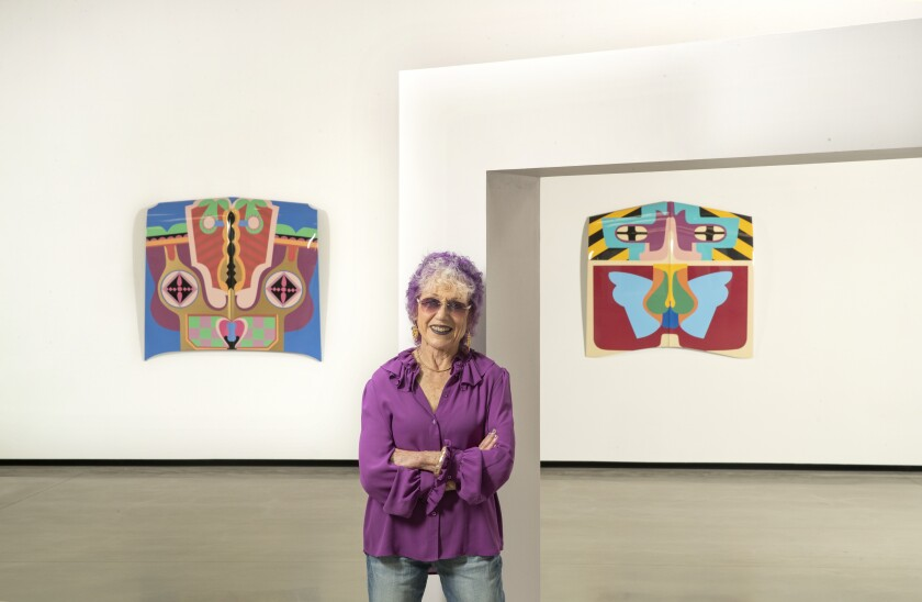 Judy Chicago in front of two pieces of art hanging on a gallery wall.