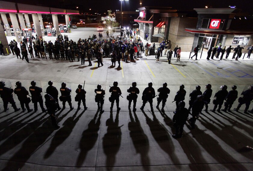 Police officers in riot gear hold a line in October 2014 as they watch demonstrators in St. Louis protest the shooting deaths of Michael Brown and VonDerrit Myers Jr.