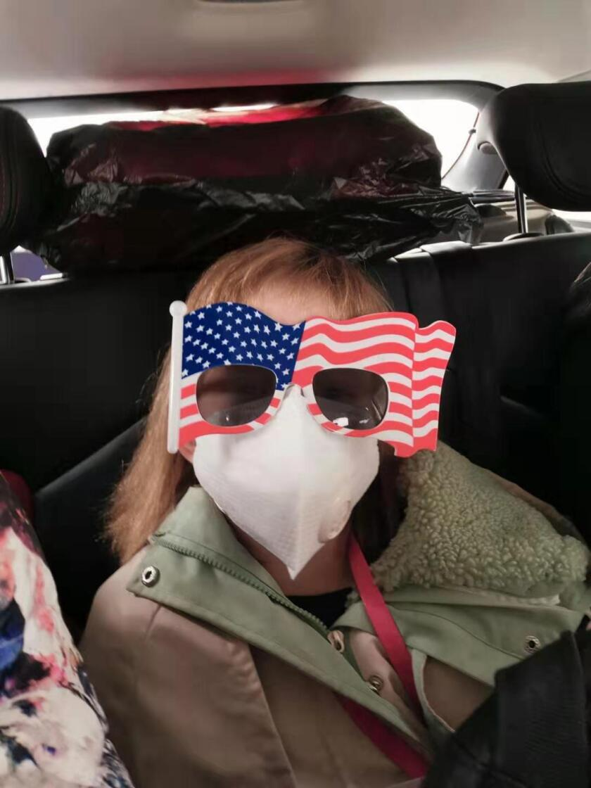 An 8-year-old American rides in a car on her way to Wuhan Tianhe International Airport for a U.S. evacuation flight Tuesday.