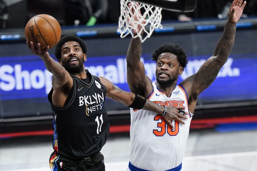 Brooklyn Nets' Kyrie Irving (11) drives past New York Knicks' Julius Randle (30) during the first half of an NBA basketball game Monday, April 5, 2021, in New York. (AP Photo/Frank Franklin II)