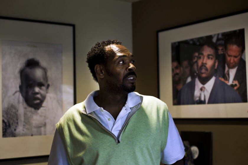 In his Rialto home, Rodney King looks at a photograph of himselffrom May 1, 1992, the third day of the Los Angeles riots.