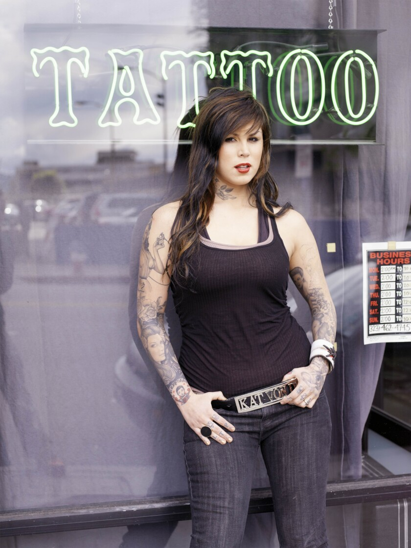 """Kat Von D on """"Miami Ink"""" in front of a storefront with a neon """"TATTOO"""" sign."""