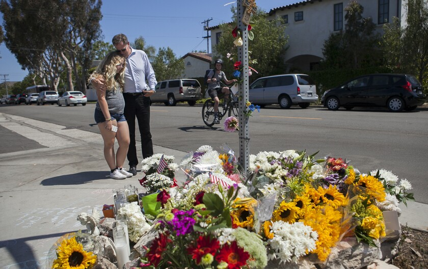 Kent Barkouras and his daughter Sara pause in May at a makeshift memorial at 15th Street and Michael Place in Newport Beach, where 8-year-old Brock McCann was struck and killed by a trash truck. The city plans to put a stop sign on Michael Place at the intersection.