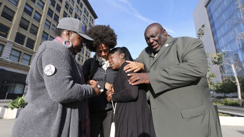 Lisa Hines, center, is comforted outside LAPD headquarters prior to a Police Commission meeting on the death of her daughter.