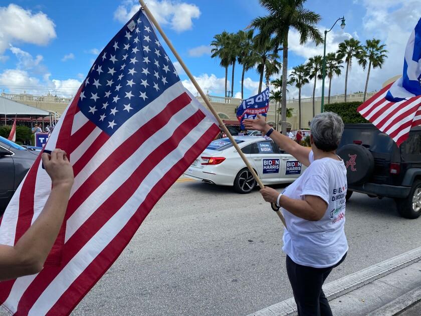 Maria Lourdes Naranjo, waves a American flag at Biden caravan, October 18, in Miami, Fla.