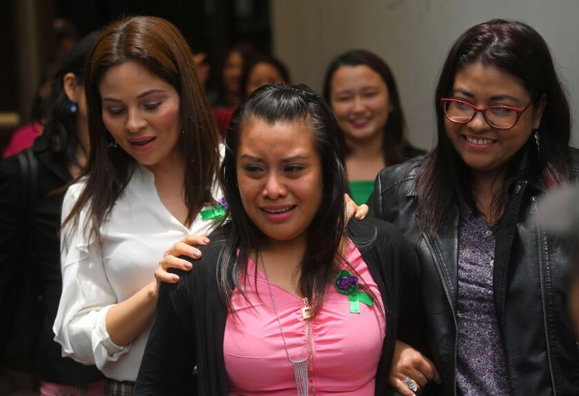 Evelyn Hernandez, center, is accompanied by her lawyers Aug. 19 in San Salvador after being acquitted of homicide in a case that drew attention to El Salvador's strict abortion laws.
