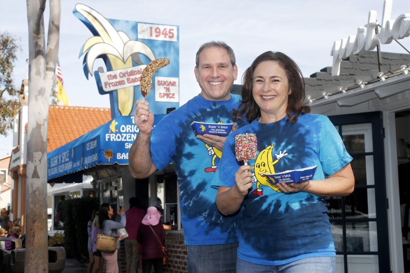 Owners Will and Courtney Alovis pose with iconic treats offered at their business, Sugar 'n Spice, which calls itself the home of the original frozen banana. The shop is celebrating 75 years on Balboa Island in Newport Beach.