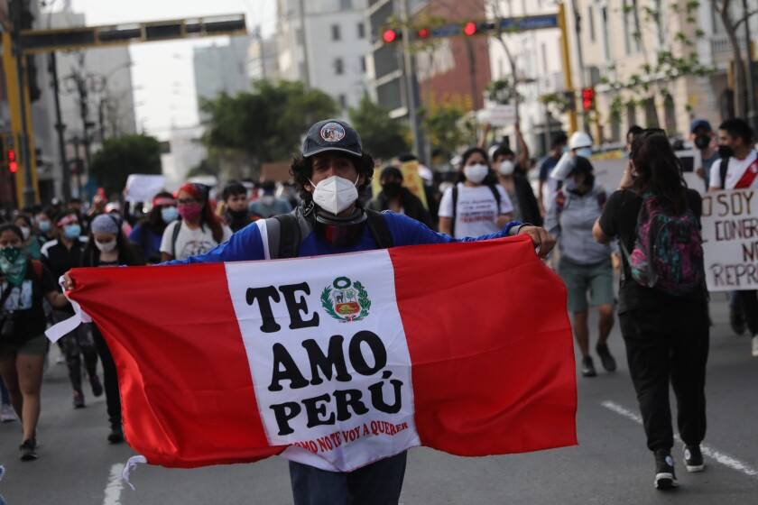 """A supporter of ousted Peruvian President Martín Vizcarra holding a banner reading """"I love you Peru."""""""
