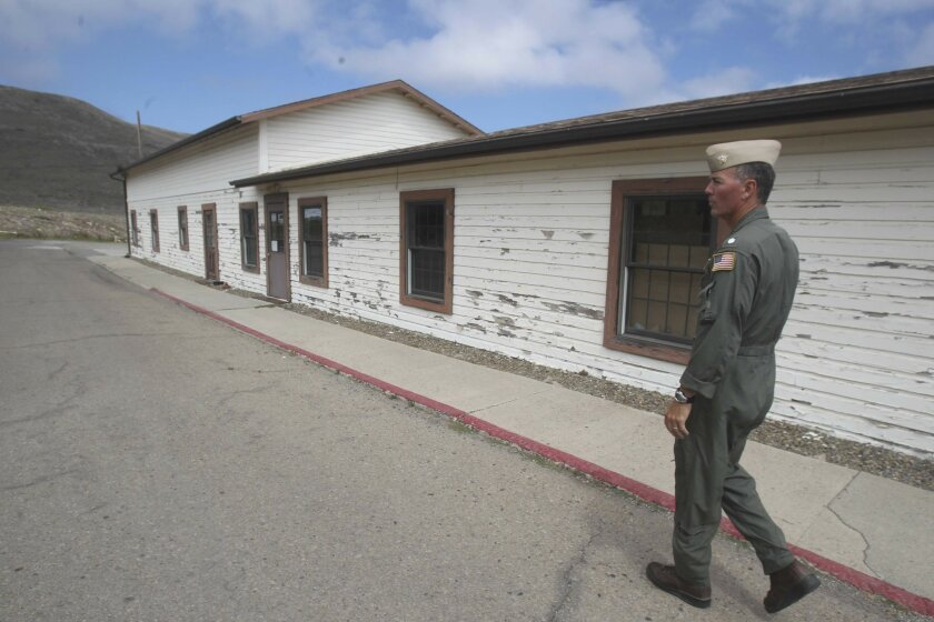 "Cmdr. Walt Glenn, ""mayor"" of San Clemente Island auxiliary air base, walks past one of the World War II-vintage buildings on the island. JOHN GIBBINS • U-T"