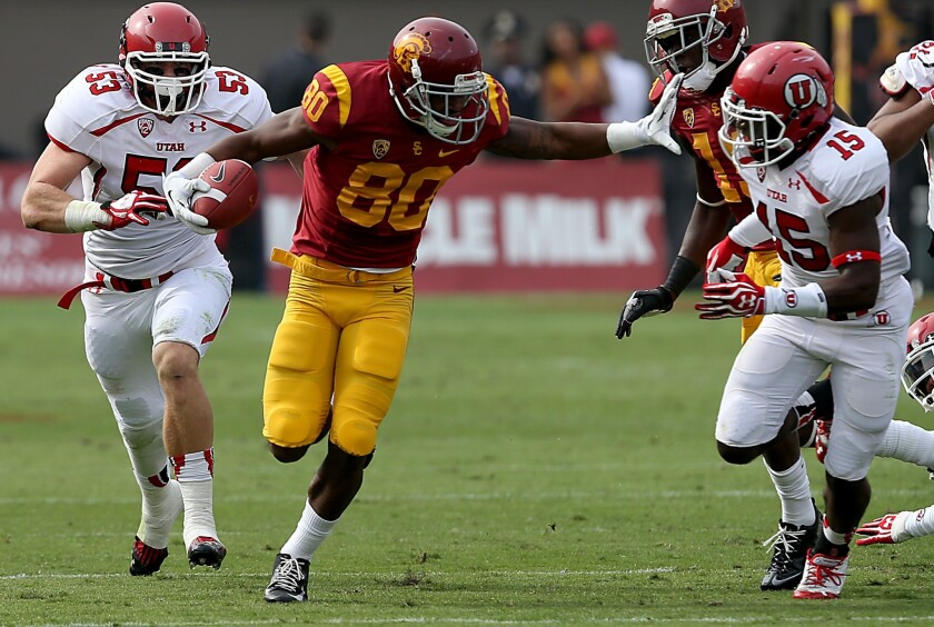 USC wide receiver De'Von Flournoy tries to sprint past Utah defenders following a second-quarter reception during the Trojans' win over Utah on Saturday.