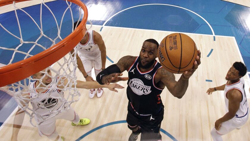 LeBron James drives for a layup against Stephen Curry during the second half of the NBA All-Star game.