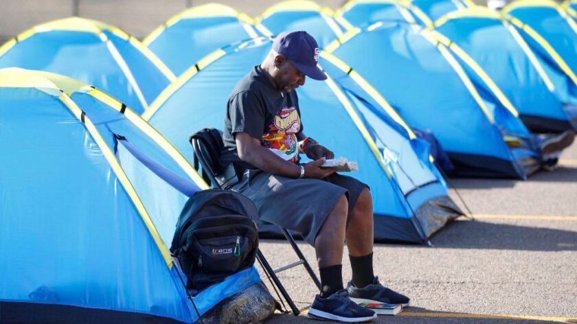 Kevin Tate, 62, shown reading a bible, was one of the first people to take up a tent at the city-sanctioned homeless camp near Balboa Park Golf Course on Oct. 12 2017. (Photo by K.C. Alfred/The San Diego Union-Tribune)
