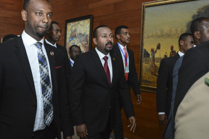 FILE - In this Sunday, Feb. 9, 2020, file photo, Ethiopia's Prime Minister Abiy Ahmed, center, arrives for the opening session of the 33rd African Union (AU) Summit at the AU headquarters in Addis Ababa, Ethiopia. Ahmed left Ethiopians breathless when he became the prime minister in 2018, introducing a wave of political reforms in the long-repressive country and announcing a shocking peace with enemy Eritrea. Now, Abiy is waging war in the defiant Tigray region. (AP Photo/File)