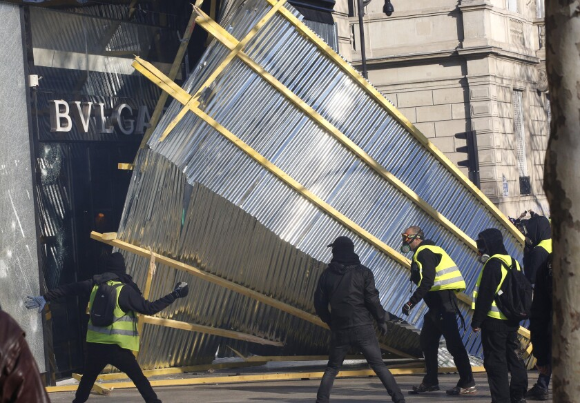Protesters tear down a protective wall in front of a luxury shop during a demonstration in Paris.