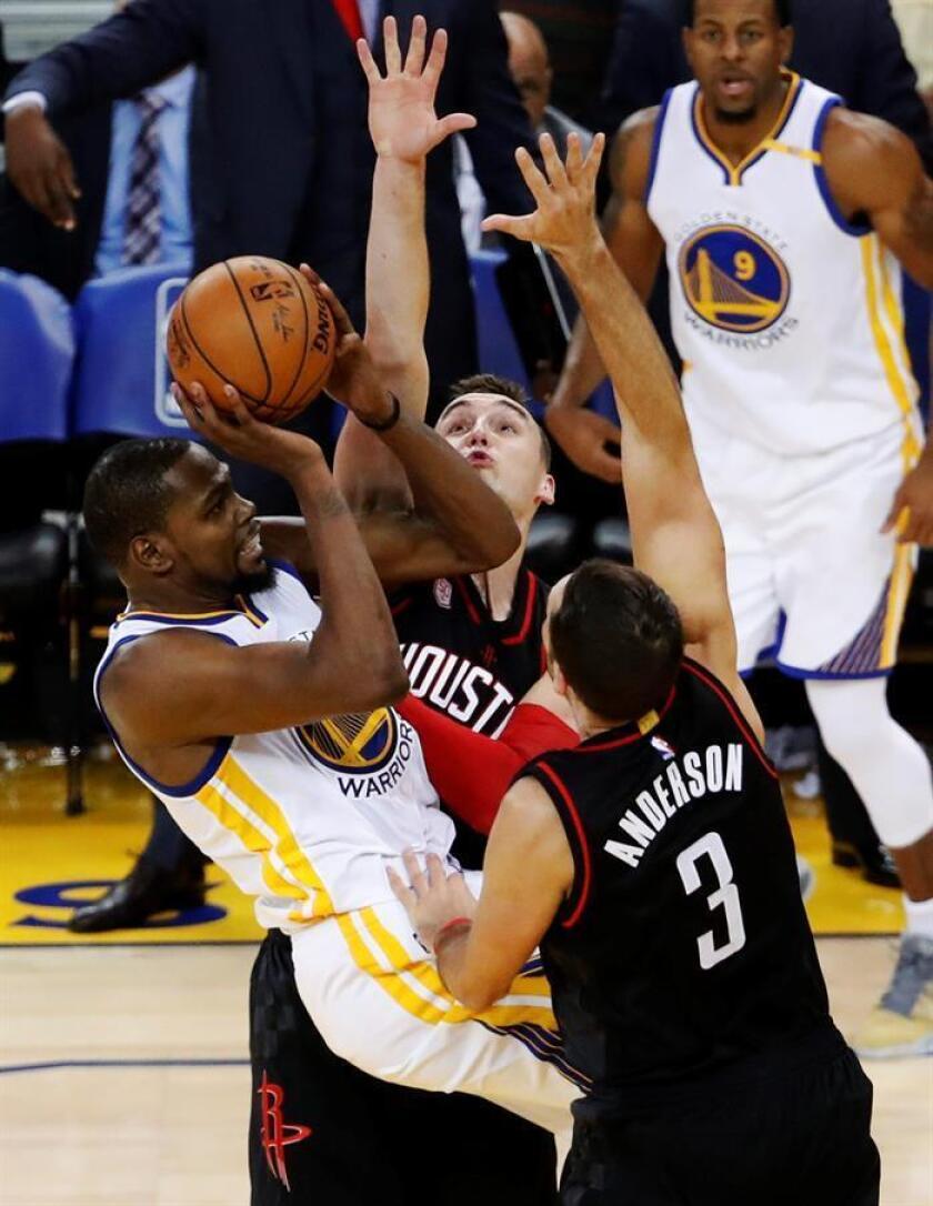 El jugador de los Golden State Warriors Kevin Durant (i) lucha por el balón con Sam Dekker y Ryan Anderson (d), de los Houston Rockets, durante el partido. EFE
