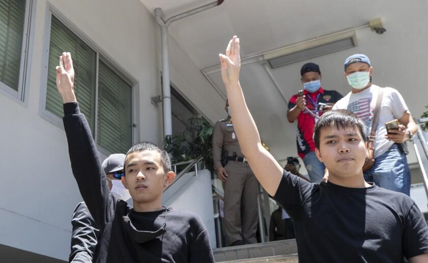 Panumas Singprom, left, and Tattep Ruangprapaikitseree raise a three-finger salute at the police station in Bangkok.