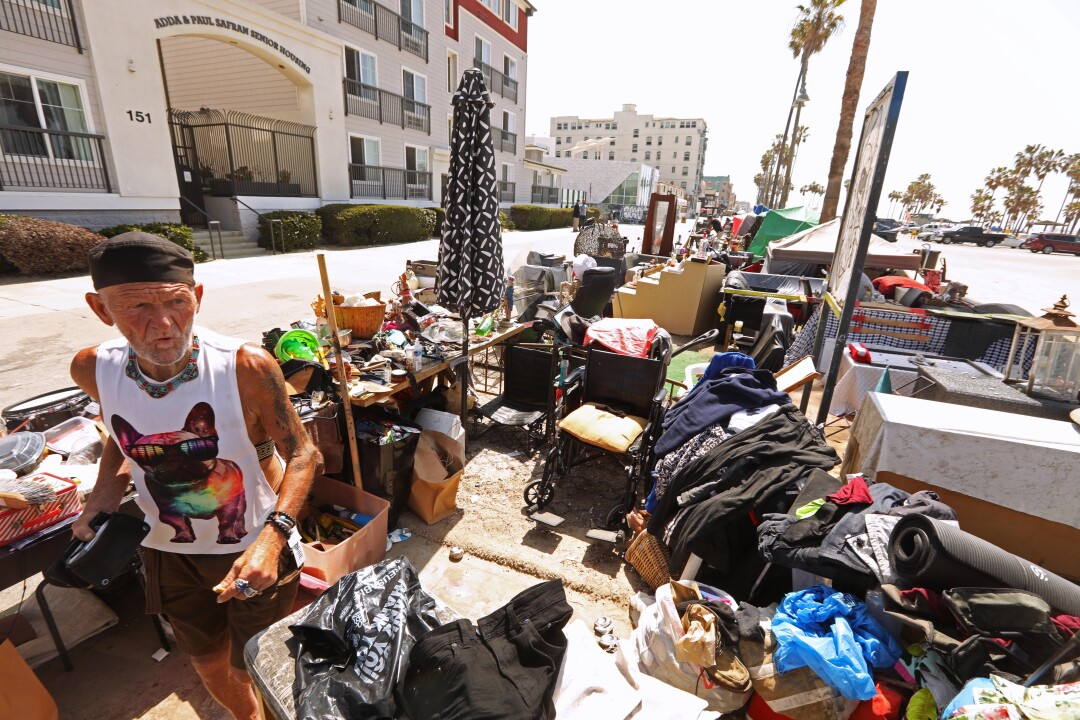 A man stands near his belongings and encampment.