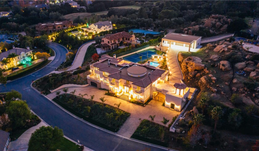 The 11,000-square-foot home comes with a pool, tennis court and custom garage with room for 14 cars.
