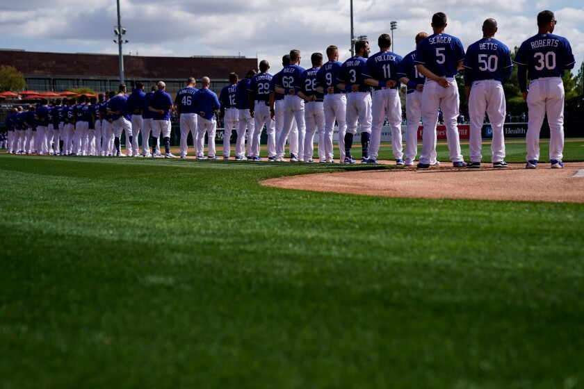 Dodgers players and coaches stand during the singing of the national anthem before a spring training game at Camelback Ranch in Arizona in February.