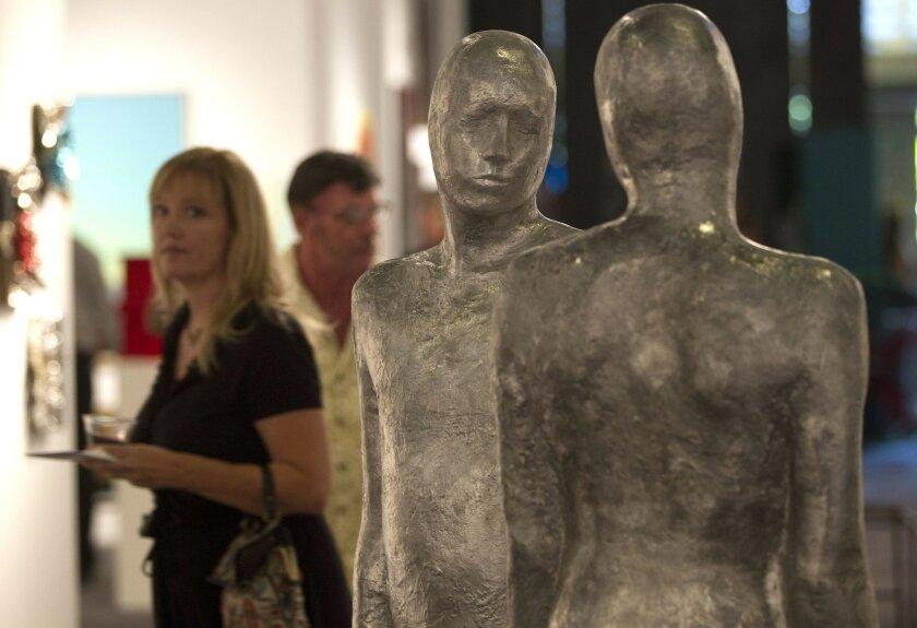 "People attending the Art San Diego Contemporary Art Fair Thursday in Balboa Park walk past the sculpture ""Counterparts"" by artist Steinunn Thorarinsdottir. The 2012 edition of the art fair features dozens of works by local artists. Sean M. Haffey • U-T"