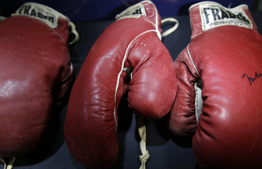"""Boxing gloves worn by Muhammad Ali and Sonny Liston are displayed in New York, Thursday, Feb. 19, 2015. Just months before the 50th anniversary of the heavyweight rematch between Ali and Liston, boxing fans are getting a chance to own a piece of one of the most hotly debated title fights of all time. Both pairs of gloves from the May 25, 1965, bout in Lewiston, Maine — won by Ali with a first-round knockout from what some saw as a """"phantom punch"""" — go up for auction Feb. 21 in New York. (AP Photo/Seth Wenig)"""