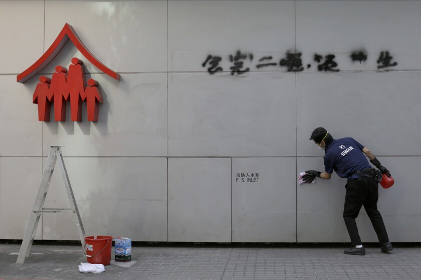 A worker cleans up a vandalized wall in Hong Kong on Monday.