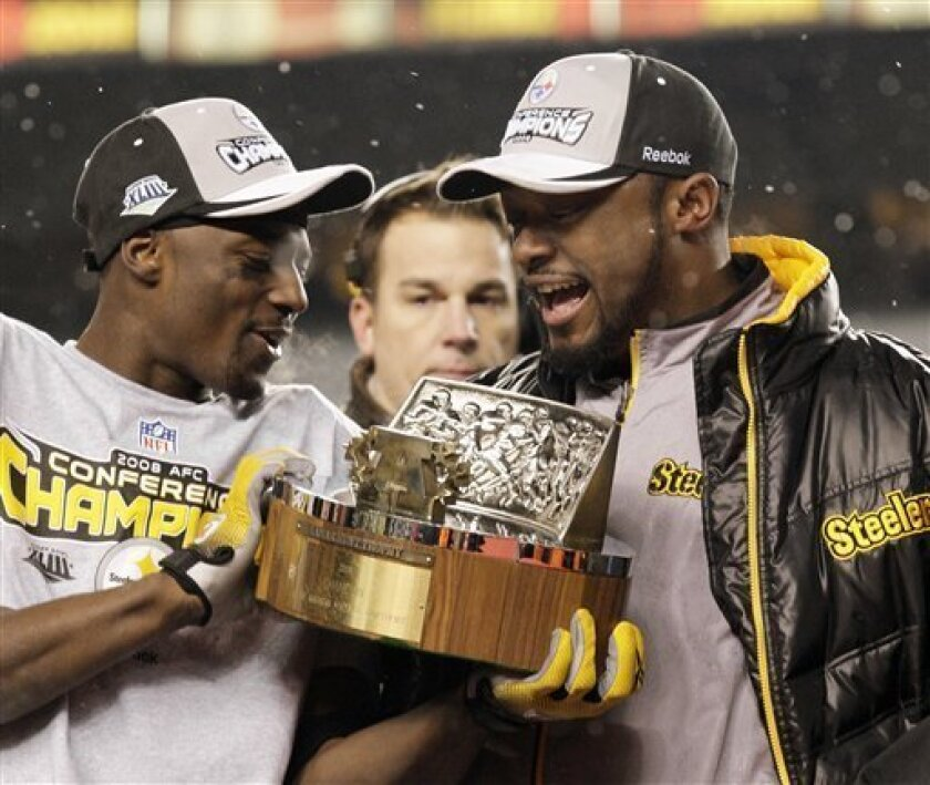 Pittsburgh Steelers wide receiver Santonio Holmes, left, holds the trophy with coach Mike Tomlin after the Steelers beat the Baltimore Ravens 23-14 in the NFL AFC championship football game in Pittsburgh, Sunday, Jan. 18, 2009. (AP Photo/Gene J. Puskar)