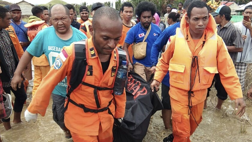 A rescue crew carries the body of a flood victim in Sentani, Indonesia.