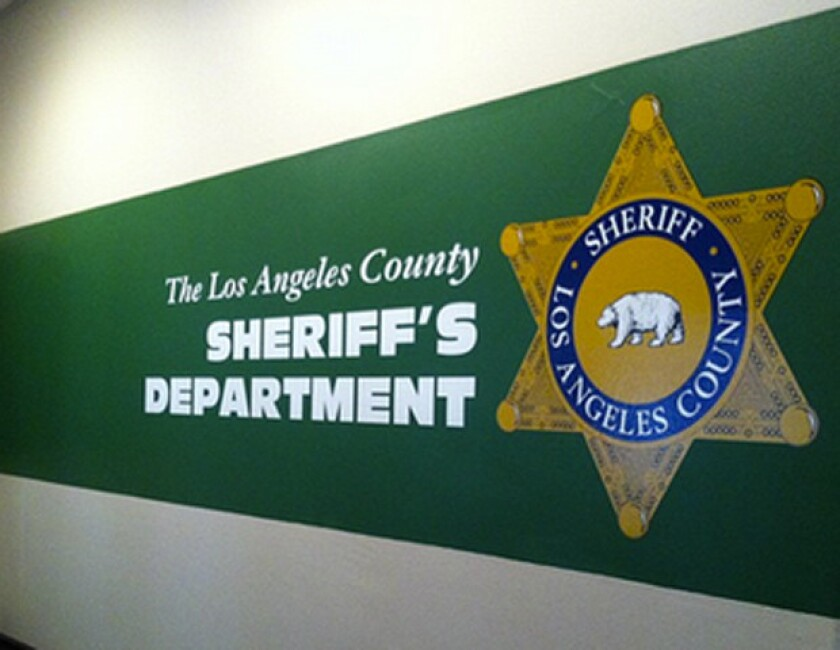 A sign for the Los Angeles County Sheriff's Department painted on a wall