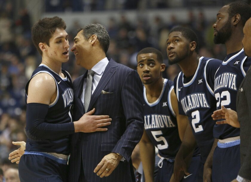 Villanova head coach Jay Wright, second from left, talks with guard Ryan Arcidiacono, left, during the second half of an NCAA college basketball game against Xavier, Saturday, Feb. 28, 2015, in Cincinnati. Villanova won 78-66. (AP Photo/David Kohl)