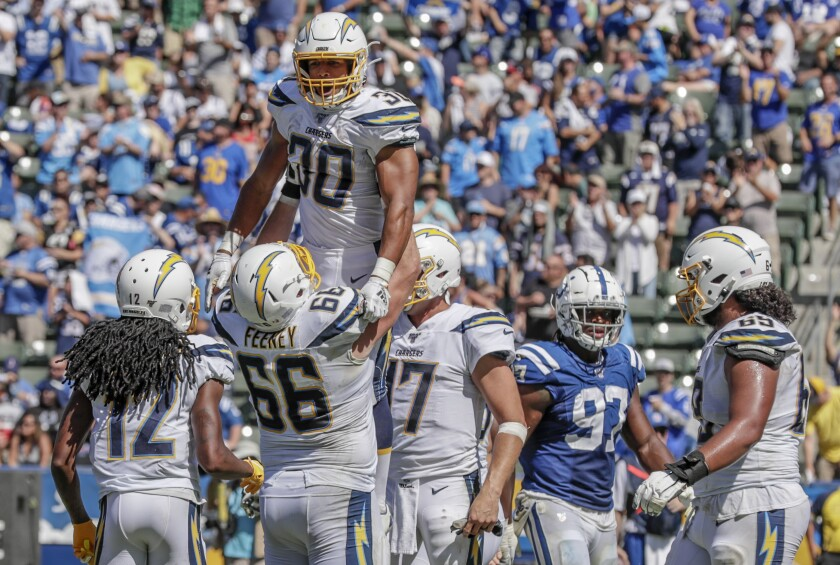 Chargers running back Austin Ekeler is hoisted by teammate Dan Feeney after scoring on a 55-yard touchdown catch Sunday.