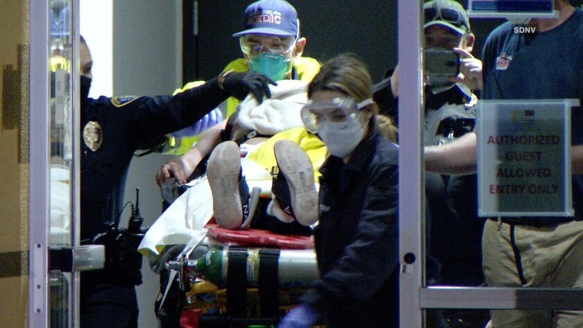 A 26-year-old woman who was shot by a San Diego police officer in an East Village apartment Saturday night is loaded into an ambulance. Police said her injury was not believed to be life threatening.
