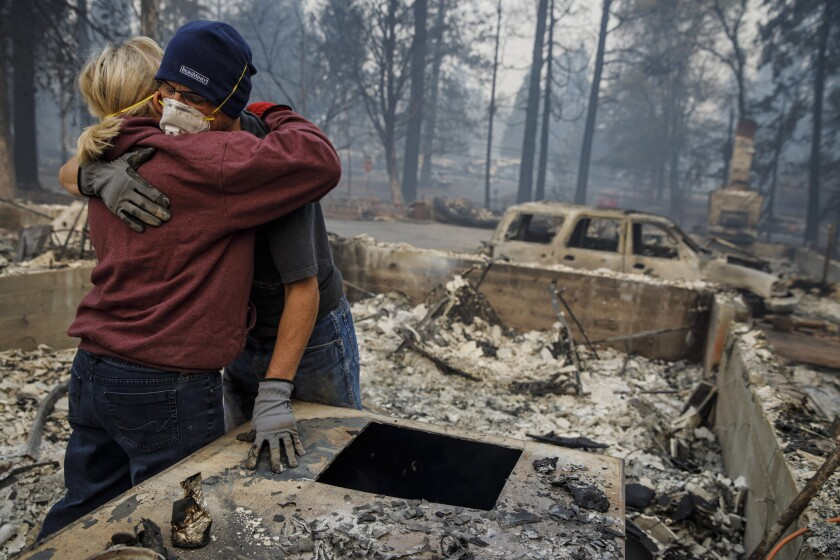 Michael John Ramirez hugs his wife, Charlie Ramirez, as they sift through the remains of their Paradise, Calif., home