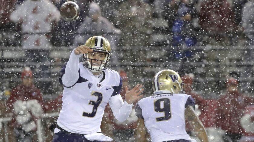 Washington quarterback Jake Browning (3) passes as running back Myles Gaskin (9) runs past him durin