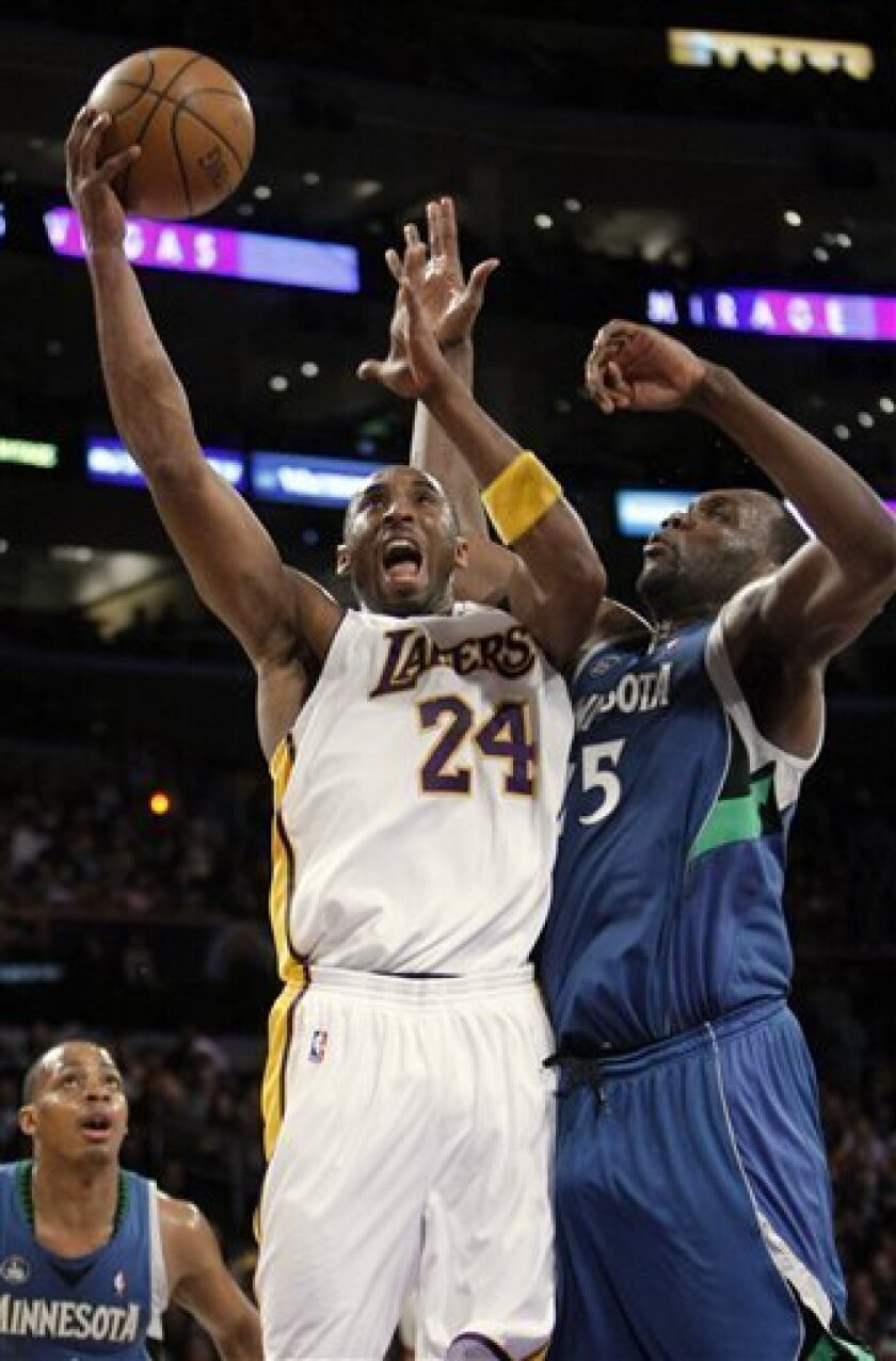 Los Angeles Lakers guard Kobe Bryant (24) puts up a shot as Minnesota Timberwolves forward Al Jefferson defends during the first half of their NBA basketball game, Sunday, Dec. 14, 2008 in Los Angeles. Minnesota Timberwolves guard Randy Foye, left, watches on. (AP Photo/Mark J. Terrill)