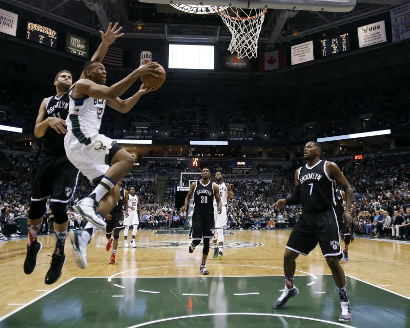 Milwaukee Bucks' Jabari Parker shoots past Brooklyn Nets' Brook Lopez during the second half of an NBA basketball game Saturday, Nov. 7, 2015, in Milwaukee. The Bucks won 94-86. (AP Photo/Morry Gash)