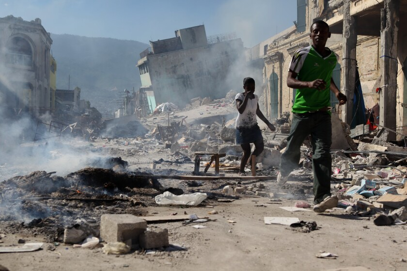 Haitians run past burning ruins in Port-au-Prince after the earthquake on Jan. 12, 2010.
