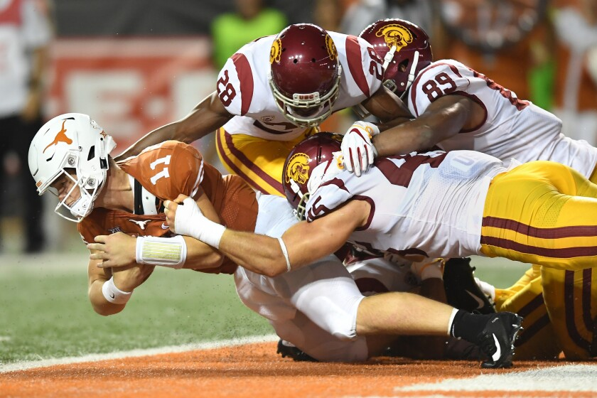 Texas quarterback Sam Ehlinger appears to be sacked in the end zone by USC's C.J. Pollard (28), Christian Rector (89) and Porter Gustin, but the ball was ruled down at the one-yard line in the second quarter at Texas on Saturday.