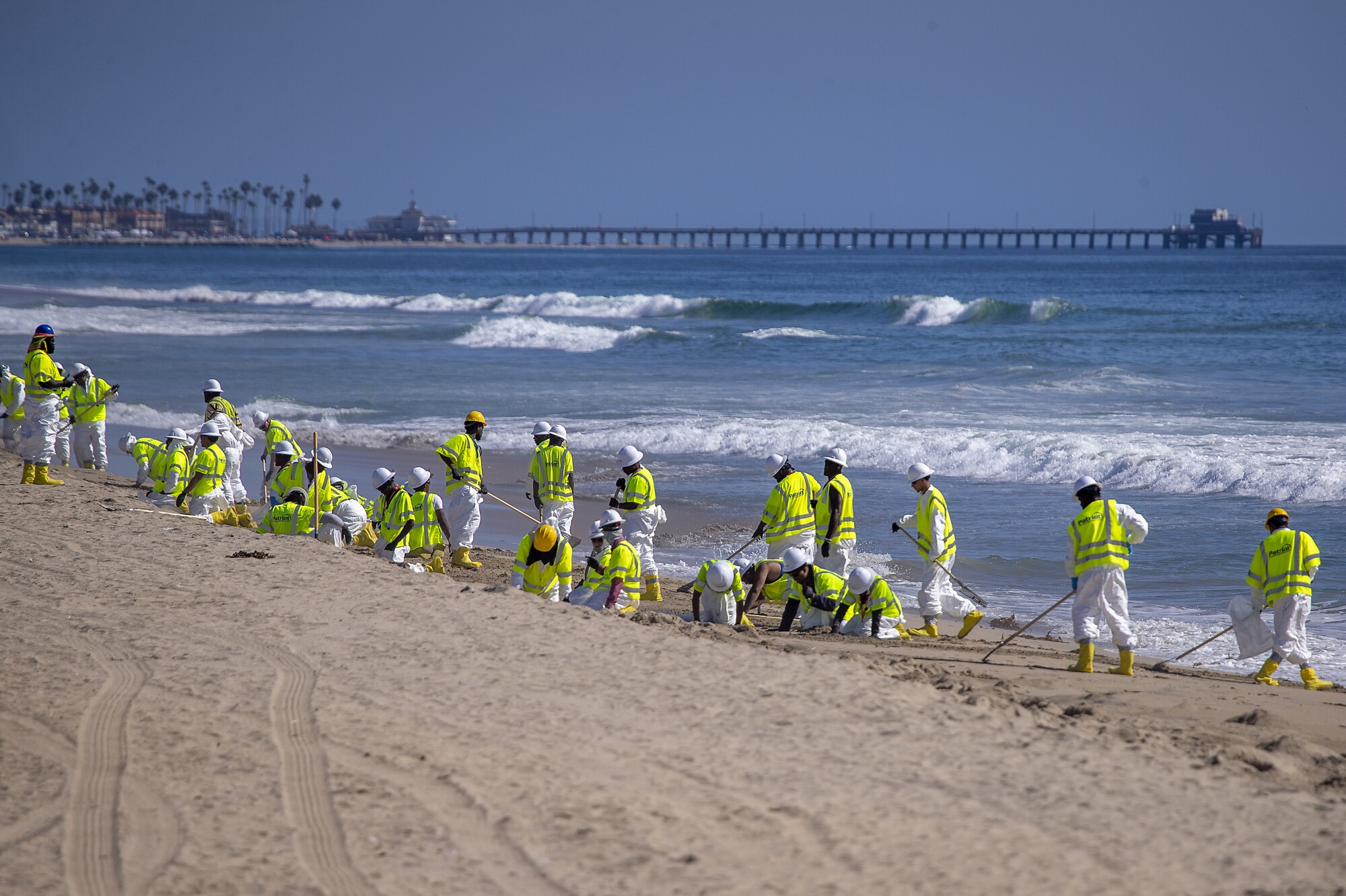 Cleanup crews in yellow vests on the beach