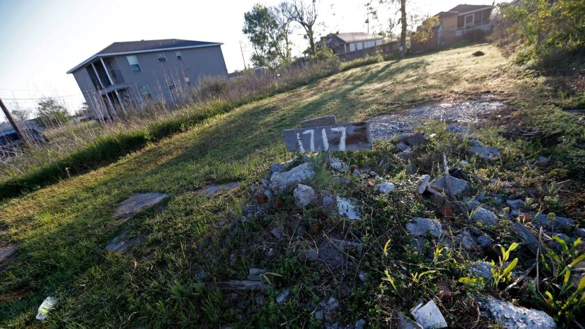 FILE - In this Thursday, March 16, 2017, file photo, rubble and an address sign mark an empty lot in