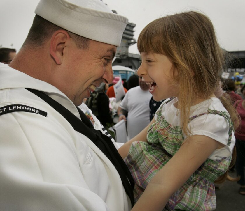Scott Callanan, a member of the USS Carl Vinson crew  left, greets his daughter, three-year-old Savannah Callanan, right, after the ship arrived at NAS North Island ending a more than six-month deployment which included the sea burial of terrorist leader Osama bin Laden and air support for troops i